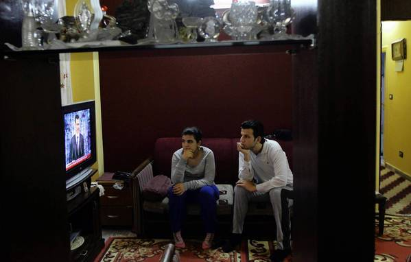 Viewers in Damascus watch Syrian President Bashar Assad speak about his own peace plan.