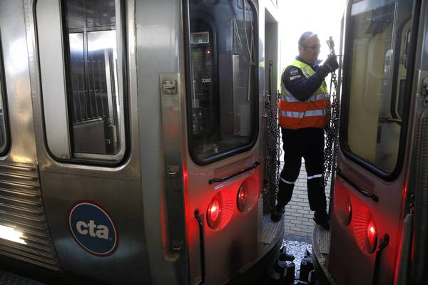 CTA switch worker Jim Doorey puts the safety chains back into place after uncoupling a train car Friday at the Brown Line's Kimball stop in Chicago. The transit agency reduces the number of cars in trains during off-peak hours to save money.
