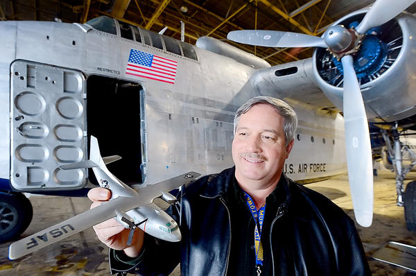 Hagerstowm Aviation Museum President John Seburn holds a model of a Fairchild C-123 Provider while standing in front of the museum's 1948 Fairchild C-82A Packet. The museum is trying to acquire a C-123 that was built in Hagerstown.