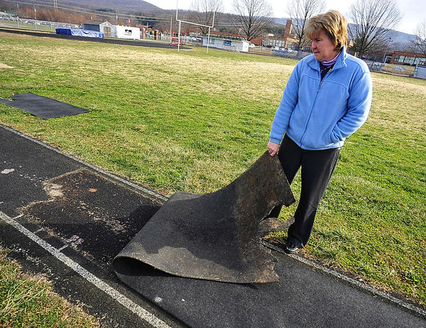 Boonsboro High School Athletic Director Sue Lowery reveals section of the track's pole vault run where the top rubberized layer has worn away. Beneath is a hard asphalt base.