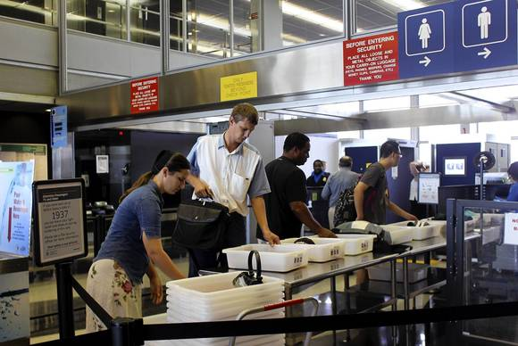 Passengers unload their items at a security checkpoint in the TSA PreCheck lane for American Airlines at Chicago's O'Hare International Airport