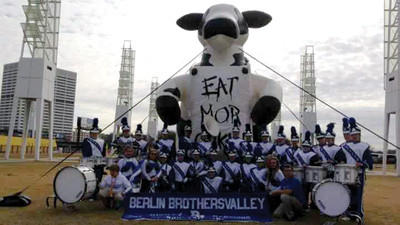 The Berlin Brothersvalley marching band poses with the iconic Chick-fil-A cow at the Chick-fil-A Bowl.