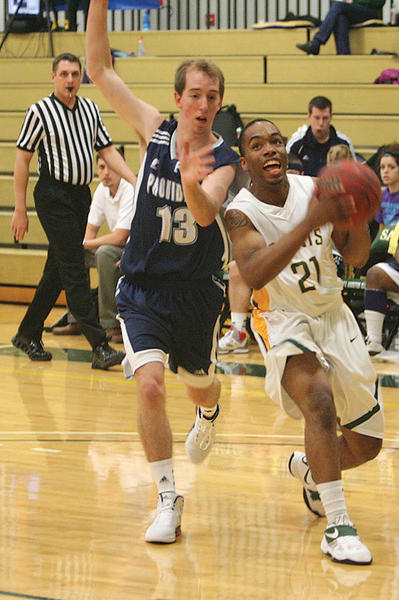 Presentation College`s Quincy Davis (21) drives to the hoop against Providence College`s Brennan Foidart (13) on Sunday at the Strode Center. American News Photo by Ryan Deal