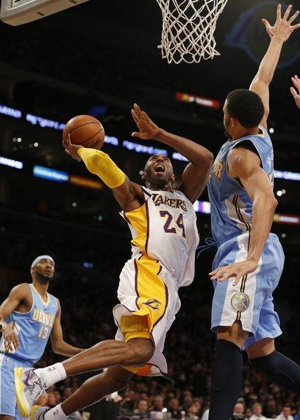 Kobe Bryant contorts his body to shoot over Nuggets defender JaVale McGee.