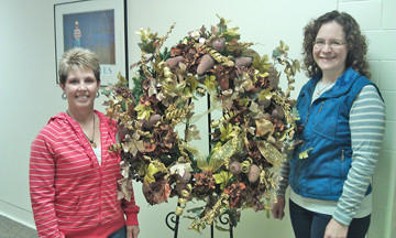 Kim Sauvage, left, shows off her holiday wreath from Kathleen's to Gretchen Sharp, the executive director of the Aberdeen Public Schools Foundation. Sauvage won the wreath during a raffle at the recent Aberdeen Public Schools Foundation Home for the Holidays Tour. The raffle item was sponsored by Jason and Cheryl Lorenz.