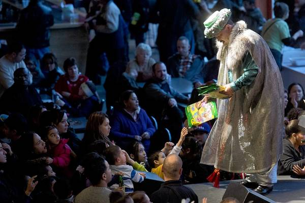 The three kings hand out presents to the waiting hands in the crowd as people take part in the Three Kings Day celebration at SteelStacks on Sunday.