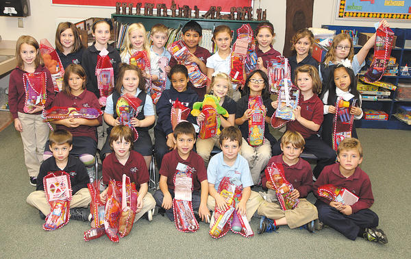 The second-grade class at Grace Academy was the first to stuff 12 Christmas stockings for The Salvation Army children. Front row, from left, Ethan Enterline, Maxwell Propst, Max Bloess, Thomas Fink, Javan Myers and Joey Salovich. Middle row, Alex Foreman (standing), Jillian Brown (sitting), Bailey Hall, Cassidy Driver, Hannah Casto, Mia Libby, Madeline Kesselring and Noelle Cunningham. Back row, Lauren Kane, Amanda Sweeney, Lauren Leather, Samuel Shoemaker, Raj Saxena, Madelyn Palank, Bethany Grach, Carter Daughtridge and Madison Wallech.