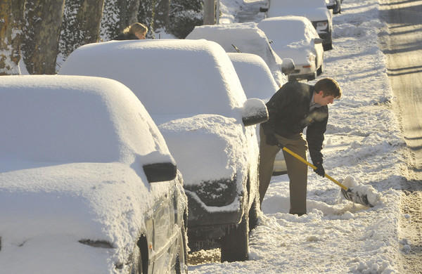 Colin Casler shovels around his car in the 700 block of E. Lake Avenue to get to work. Morning sunshine and clear skies make it easier for people to dig out from the five to seven inches of snow that fell overnight in the Baltimore region. Area schools were closed.