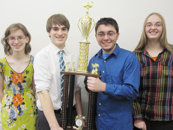 Petoskey High School 2013 Tier 1 state debate champions, (from left) Megan Keller, Jackson Burek, Eli Ellison and Paige Petrowski, hold the championship trophy immediately following their weekend win at the 96th annual debate state finals at Eastern Michigan University in Ypsilanti.