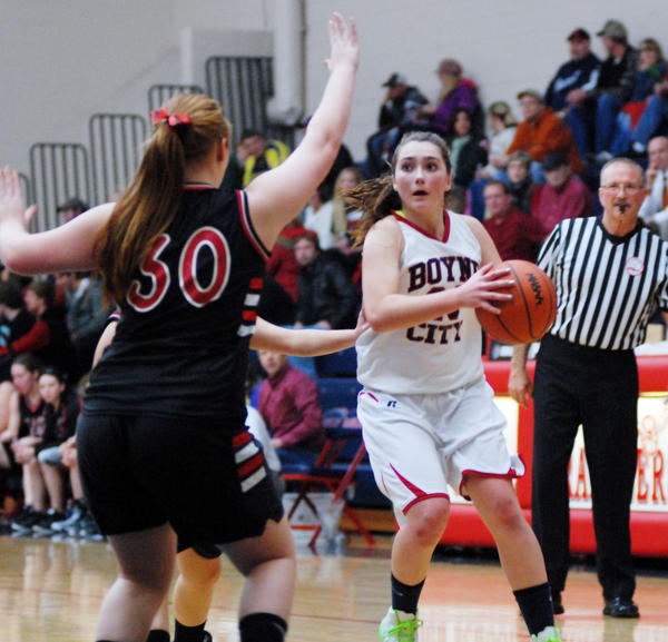 Boyne City's Rainy McCune (right) looks inside as she's defended by East Jordan's Allie Sutton defends during Friday's Lake Michigan Conference contest at the Boyne City High School gym.
