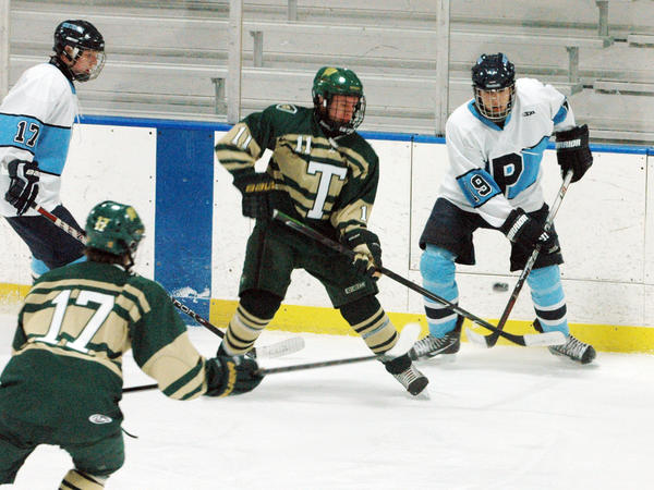 Petoskey senior forward Brandon Pomranke (right) flips a pass past Traverse City West's Trevor Franklin during Friday's Big North Conference contest at Griffin Arena. The Titans defeated the Northmen, 4-3, in overtime.