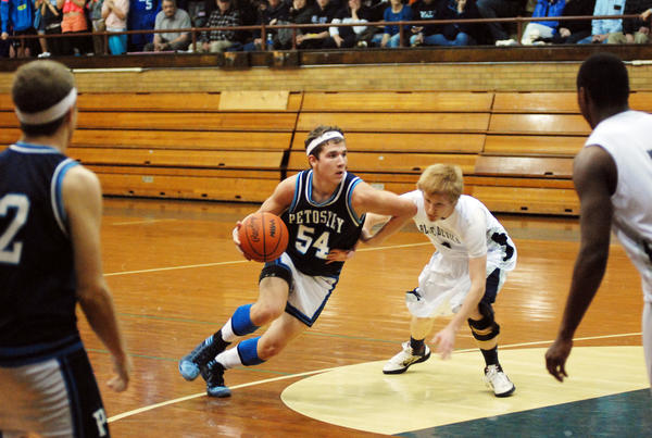 Petoskey senior guard Sam Baumgartner (left) drives past Sault Ste. Marie senior John Seeley during the first half of Friday's non-league contest at the Petoskey Central Elementary School gym. Baumgartner had a career-high 30 points as the Northmen defeated the Blue Devils, 69-47, in the 1980s Throwback Game.