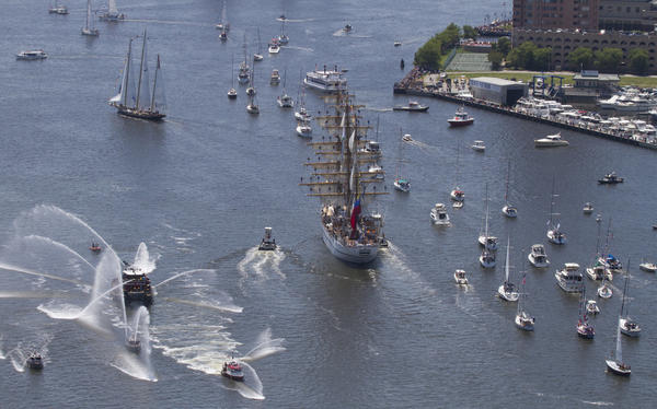 A flotilla trails as tugs greet tall ships entering downtown Norfolk during the OpSail 2012 parade of sail on Friday.