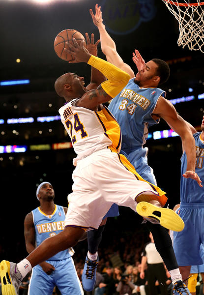 Kobe Bryant #24 of the Los Angeles Lakers goes up for a shot against JaVale McGee #34 of the Denver Nuggets at Staples Center on January 6, 2013 in Los Angeles, California.