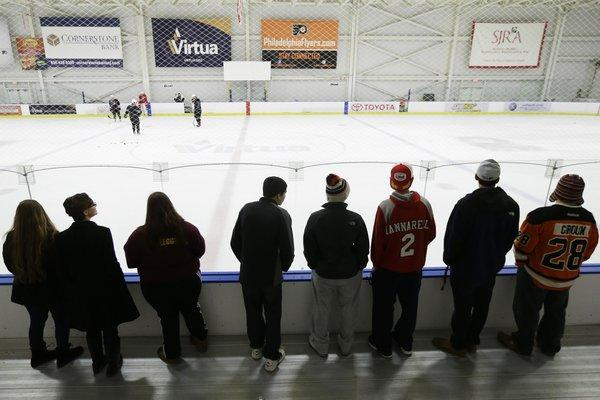 Hockey fans watch players practice at the Philadelphia Flyers' training facility Monday, a day after a tentative deal was struck to end the labor dispute that had threatened to wipe out the entire season.