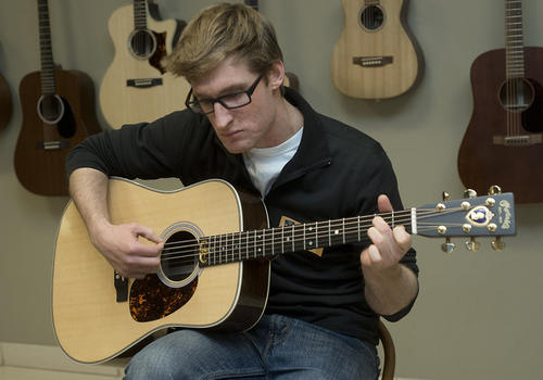Brad Snyder of Baltimore strums a custom Martin Guitar presented to him inside the Nazareth guitar maker's headquarters on Monday. Lt. Brad Snyder was blinded by an IED blast while serving with the armed forces in Afghanistan in September of 2011.