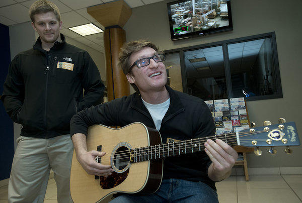 Brad Snyder of Baltimore (right) strums his new custom guitar, next to friend John Keirle of Bethlehem, (left) after Snyder was presented a custom Martin Guitar inside the Nazareth guitar maker's headquarters on Monday. Lt. Brad Snyder was blinded by an IED blast while serving with the armed forces in Afghanistan in September of 2011.