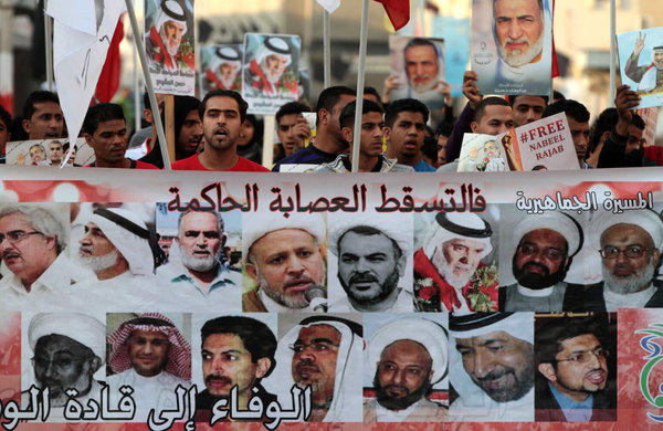 Bahraini protesters in Malkiya village chant antigovernment slogans as they hold a banner with images of jailed opposition leaders.