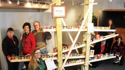 Members of the Arts Coalition of the Alleghenies stand beside a sculpture by Barry Poglein inside Bottle Works Ethnic Arts Center in Cambria City. Pictured from left are Theresa Gay-Rohall from ART WORKS in Johnstown!, Rebecca Catelinet of the Pennsylvania Rural Arts Alliance, Theresa Marafino from the Mountain Playhouse, Michael Bodolosky of the Pasquerella Performing Arts Center, Patricia Hofscher of the Johnstown Symphony Orchestra, and Stephanie Collis and Rosemary Pawlowski of Bottle Works. Artist: Barry Poglein # Cans: 105 total (some of them were brought over from ARTWORKS) Sculpture: Can-da-leever The can donations didnt really pour in until the last day, so in lieu of an actual sculpture, Poglein created an interactive piece. Ive attached the instructions to give you some idea of how it works. Basically, when a family drops off their canned good, they place it on the track and let it roll. The objective is for ones can to make it to the end, ring the bells, and drop into the snowmans basket. People seemed to have quite a bit of fun.