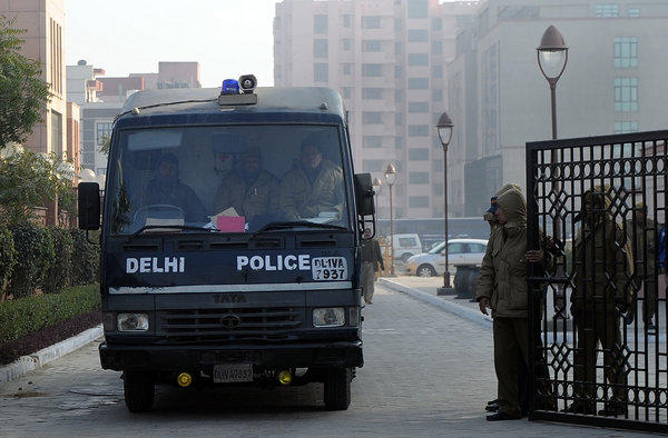 Indian police personnel escort a prisoner transport vehicle after the men accused in a gang rape and murder case were presented in Saket District Court in New Delhi.