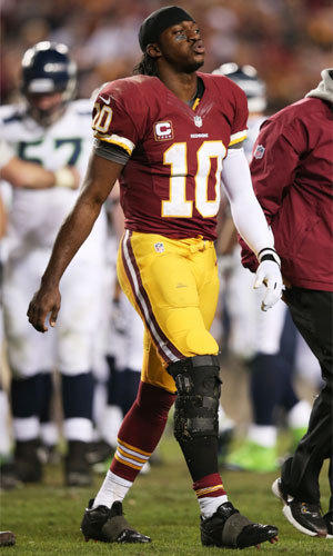 Washington quarterback Robert Griffin III leaves the field injured during the Redskins' 24-14 loss to Seattle on Sunday.