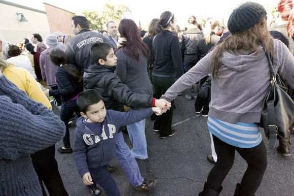 A parent leads her children away from an pickup area after R.D White Elementary School was evacuated due to a bomb threat on Monday, January 7, 2013.