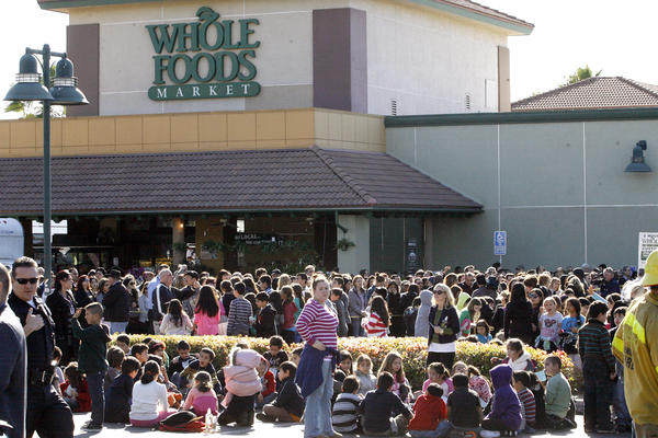 R.D White Elementary School gather in an evacuation area in the Whole Foods parking lot after the school was evacuated due to a bomb threat on Monday, January 7, 2013.