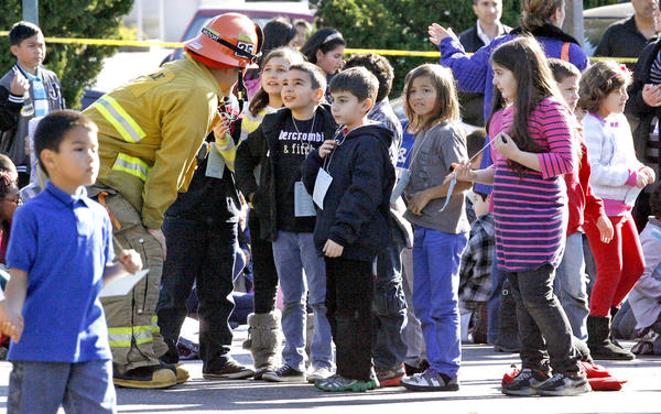 A Glendale firefighter talks to R.D White Elementary School students in the Whole Foods parking lot after the school was evacuated due to a bomb threat on Monday, January 7, 2013.