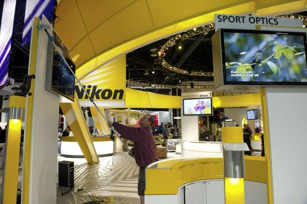 A worker cleans Nikon signage.