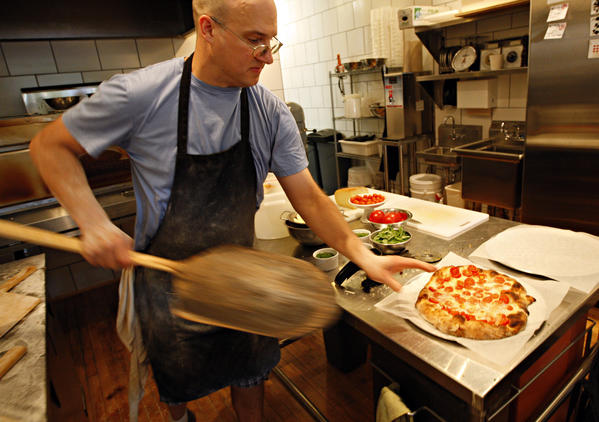 Nick Lessins pulls a pizza with tomato, fresh cream, garlic, dante and fresh herbs out of the oven at Great Lake pizza in Andersonville on Thursday, August 13, 2009. The restaurant will close sometime this month.