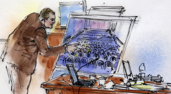 This courtroom sketch shows Aurora Police Detective Matthew Ingui pointing to a large photograph of the inside of the Century 16 theater.
