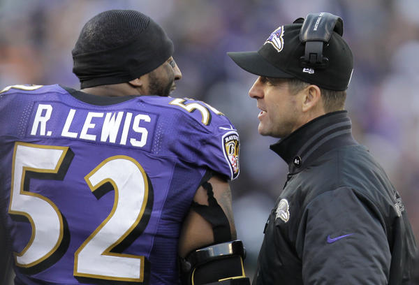 Ravens coach John Harbaugh chats with Ray Lewis during Sunday's AFC wild-card game against the Colts.