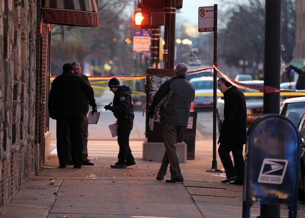 Chicago Police conduct an investigation at the scene of an officer-involved shooting at 75th Street and Jeffery Boulevard in Chicago today.