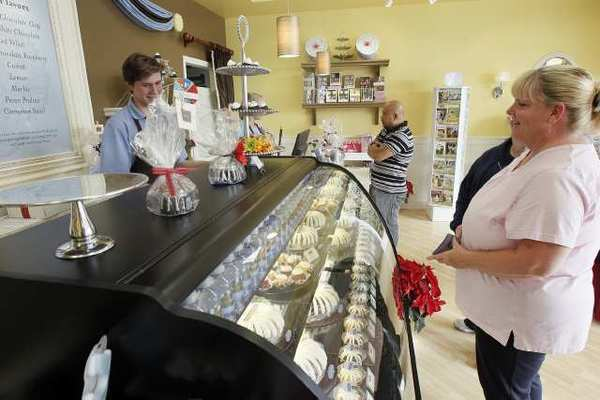 Blake Rottiers, left, helps customers at Nothing Bundt Cakes in Huntington Beach in December.