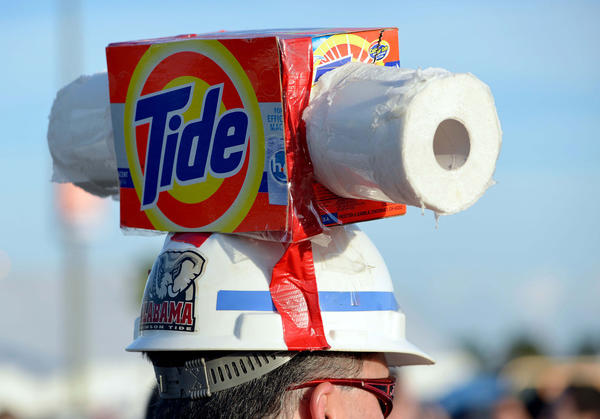 "A fan of the Alabama Crimson Tide wears a box of Tide and toilet paper representing the phrase ""roll tide, roll"" walks outside of the stadium before the 2013 BCS Championship game against the Notre Dame Fighting Irish at Sun Life Stadium."