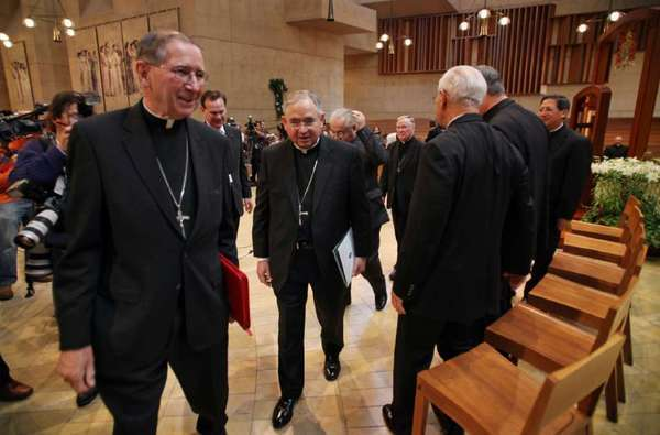 Cardinal Roger Mahony, left, and Archbishop Jose Gomez, who succeeded him as head of the Los Angeles Archdiocese, depart a press conference at the Cathedral of Our Lady of the Angels today.