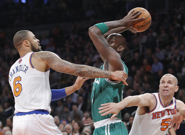 Boston Celtics forward Kevin Garnett looks to pass the ball surrounded by New York Knicks center Tyson Chandler (6) and guard Jason Kidd (5) in the first quarter.