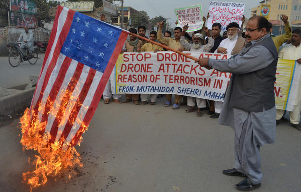 A demonstrator holds up a burning US flag during a protest against drone attacks in Pakistan.