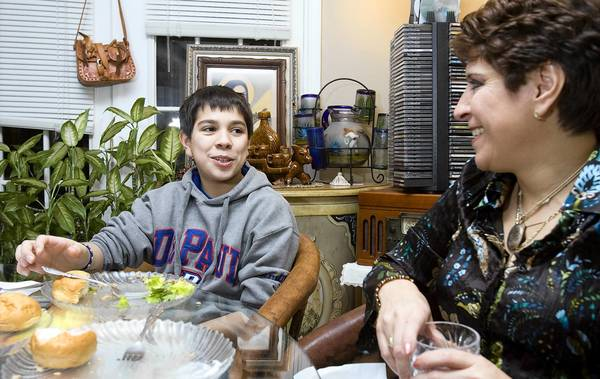 Hector Rodriguez Jr. , 12, and his mother, Martha Rodriguez, finish an evening meal that features a lean turkey–vegetable mix, salad, raw vegetables and bread. Martha Rodriguez participates in a program called FitKids that emphasizes healthy dietary choices and physical activity patterns.