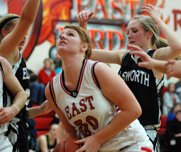 East Jordan forward Allie Sutton (middle) is surrounded under the basket by Ellsworths Kari Steenwyk (left) and Tara Essenberg (right) Monday at the East Jordan High School gym.