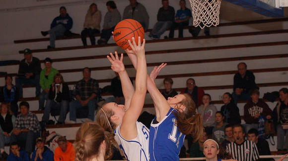 BEKAH MYLER BATTLES for the ball with Inland Lakes' Sandy Bischoff. Myler and the Snowbirds held Bischoff, the Bulldogs¿ leading scorer, to 10 points during the 60-30 St. Mary victory on Saturday.