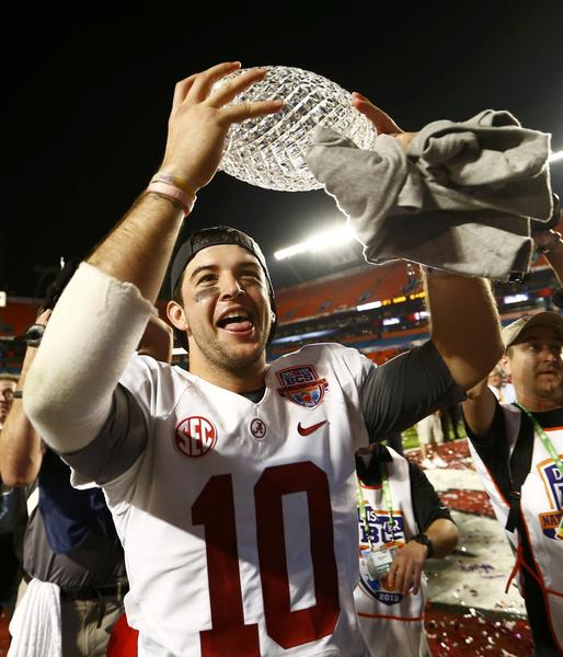 Alabama Crimson Tide quarterback AJ McCarron celebrates with the trophy after his team defeated the Notre Dame Fighting Irish in their NCAA BCS National Championship college football game in Miami, Florida, January 7, 2013.