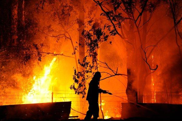 A firefighter wearing protective clothing is nearly surrounded by flames as he protects a property being threatened by the Dean's Gully fire near the town of Wandandian in New South Wales, Australia, on Tuesday.