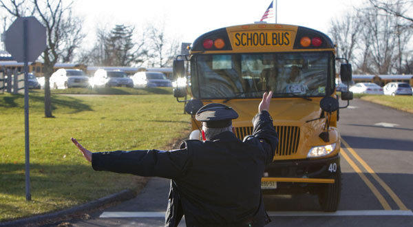 A Marlboro Township, N.J., police officer directs school buses out of the Delfino Central Elementary School parking lot.