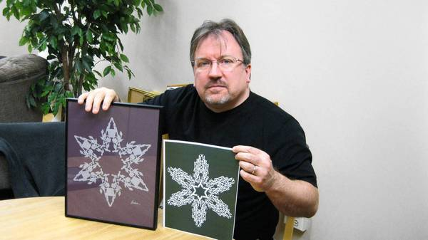 Les Barker, a web designer at Wheaton College, displays two of his many snowflake designs. The smaller piece is a replica of a design he sent to honor victims of the Newtown, Connecticut tragedy.