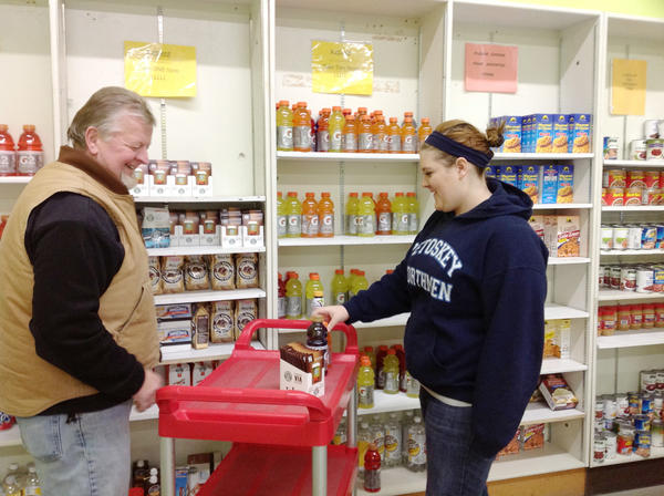 Crooked Tree High School student Kaela Ferguson works with warehouse manager Dan Cole to stock shelves in the food pantry at the Mann Food Project. Students volunteer at area organizations as part of their community-based life skills curriculum.