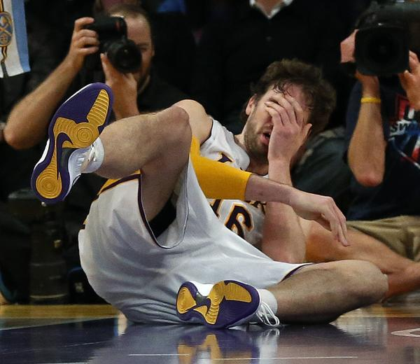 Pau Gasol falls to the floor after he is smacked in the nose by the Nuggets' JaVale McGee late in the fourth quarter of the Lakers' loss to Denver, 112-105.