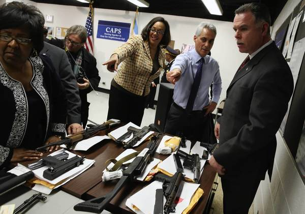 Mayor Rahm Emanuel, second from right, and Chicago police Superintendent Garry McCarthy look over a display of confiscated weapons at a news conference Tuesday. McCarthy is eager to find ways to get residents more willing to cooperate with police.