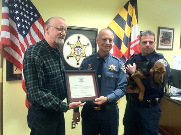 "Washington County Sheriff Douglas Mullendore presents John Reece of Hagerstown with a certificate of recognition and generosity, for his donation of 17 week-old bloodhound ""Bess"" to the Sheriff's canine program."