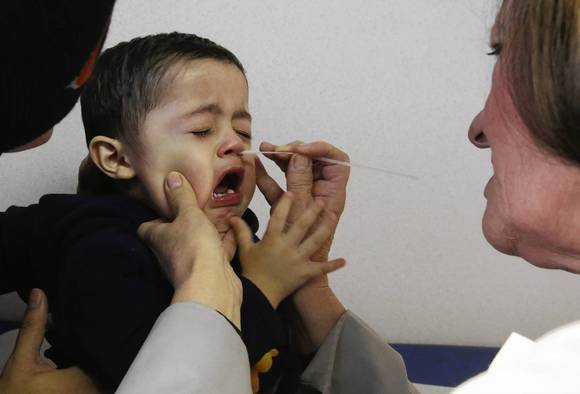 Held by his father, Raul, 18-month-old Raul Zarco receives a nasal rapid flu test from Dr. Mira Malinowska on Tuesday at Gottlieb Hospital in Melrose Park. The toddler had a fever, cough and watery eyes.